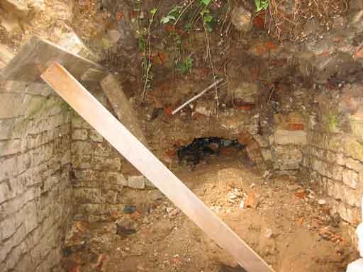 Cái miệng lò được đào ra. Rễ cây rơi lòng thòng xuống khu vực của lò